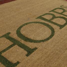 tapis coco avec découpe laser et incrustation de tapis brosse de couleur.